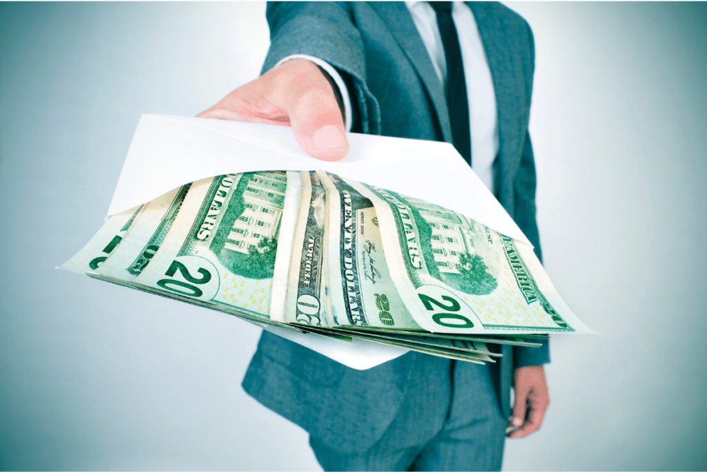 Man holding out an envelope stuffed with cash
